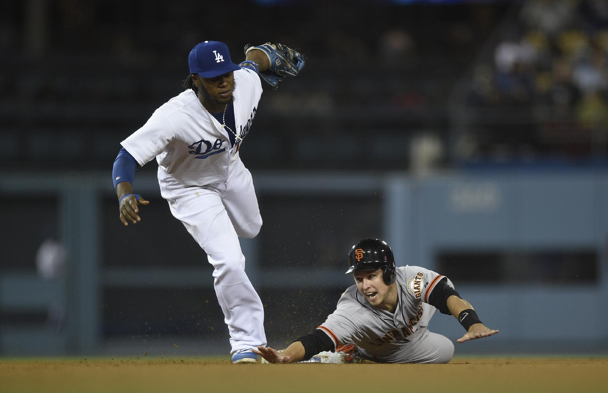 San Francisco Giants' Michael Morse, right, reacts after he is tagged out by Los Angeles Dodgers shortstop Hanley Ramirez, left, on an attempt to steal second base during the eighth inning of a baseball game in Los Angeles, Thursday, May 8, 2014