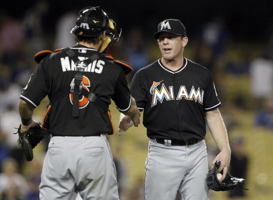Miami Marlins catcher Jeff Mathis, left, congratulates Randy Wolf in the ninth inning, after Wolf picks up the save, for pitching the last three innings, in a 13-3 win over the Los Angeles Dodgers in a baseball game on Wednesday, May 14, 2014, in Los Angeles