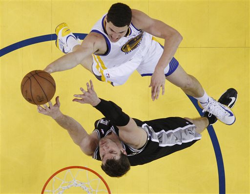 San Antonio Spurs' Tiago Splitter, bottom, defends on Golden State Warriors' Klay Thompson during the first half of Game 6 of a Western Conference semifinal NBA basketball playoff series in Oakland, Calif., Thursday, May 16, 2013. San Antonio won 94-82