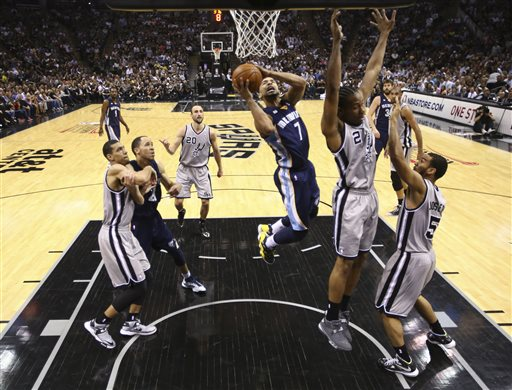 Memphis Grizzlies' Jerryd Bayless (7) goes up for a shot against the San Antonio Spurs defense during the first half in Game 2 of the Western Conference finals NBA basketball playoff series, Tuesday, May 21, 2013, in San Antonio