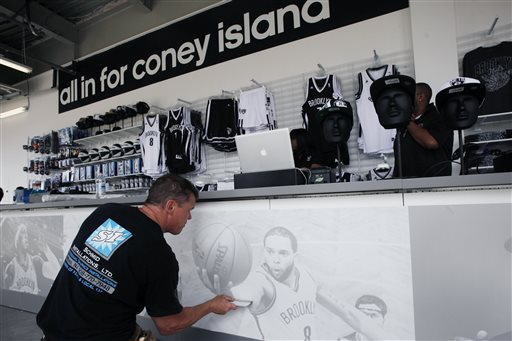 Barry Schmid applies a photo display to the sales counter inside the new Nets Shop by Adidas in the Coney Island neighborhood of Brooklyn in New York, Thursday, May 23, 2013. The shop, which carries apparel featuring the NBA basketball team Brooklyn Nets, is located within the historic boardwalk and amusement park area of the ocean front community