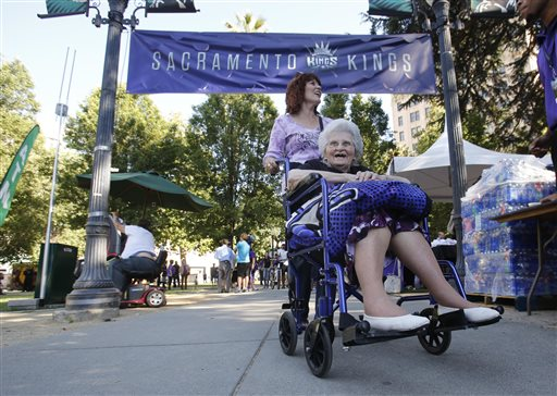 Kathy Rein wheels her mother, long time Sacramento Kings fan Catherine Henretty, 98, to Cesar Chavez Park for