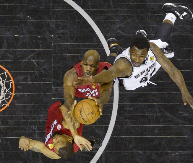 Miami Heat's Rashard Lewis, Joel Anthony (50) and San Antonio Spurs' DeJuan Blair (45) battle for a rebound during the second half at Game 3 of the NBA Finals basketball series, Tuesday, June 11, 2013, in San Antonio