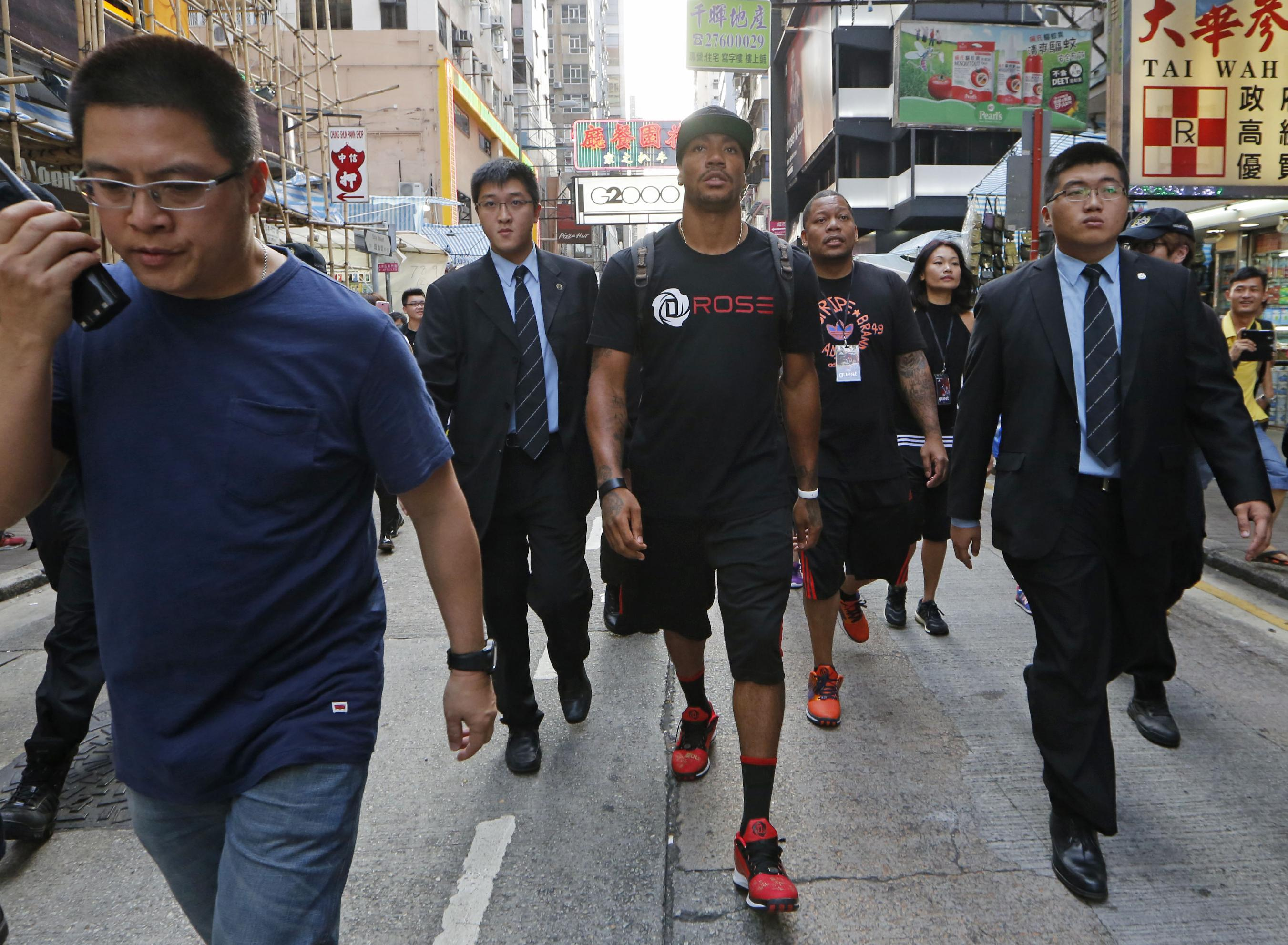 NBA star Derrick Rose of Chicago Bulls, center, walks in a shopping district in Hong Kong after attending a promotional event as part of his Asia tour Friday, Sept. 13, 2013. Rose will visit Manila, the Philippines after touring Hong Kong
