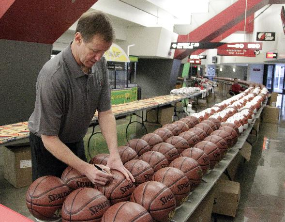 Portland Trail Blazers NBA basketball coach Terry Stotts signs one of over 350 basketballs during the Trail Blazers media day in Portland, Ore., Monday, Sept. 30, 2013