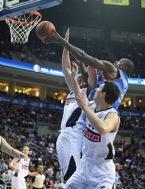 Oklahoma City Thunder's Serge Ibaka, center, and Gasper Vidmar, left, and Emir Preldzic of  Fenerbahce Ulker fight for the ball during a basketball game in Istanbul, Turkey, Saturday, Oct. 5, 2-13. Oklahoma City Thunder has opened the preseason schedule with a game against the five-time Turkish champions at the Ulker Sports Arena. (AP Photo)
