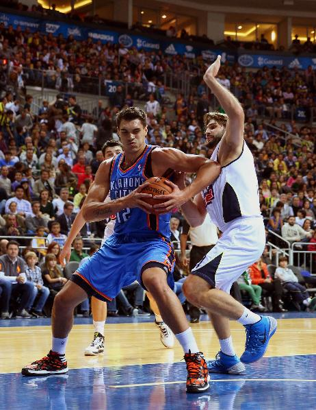 Oklahoma City Thunder's Steve Adams, left, passes the ball around Linas Kleiza of Fenerbahce Ulker fight for the ball during a preseason basketball game in Istanbul, Turkey, Saturday, Oct. 5, 2-13. Oklahoma City Thunder has opened the preseason schedule with a game against the five-time Turkish champions at the Ulker Sports Arena.  (AP Photo)