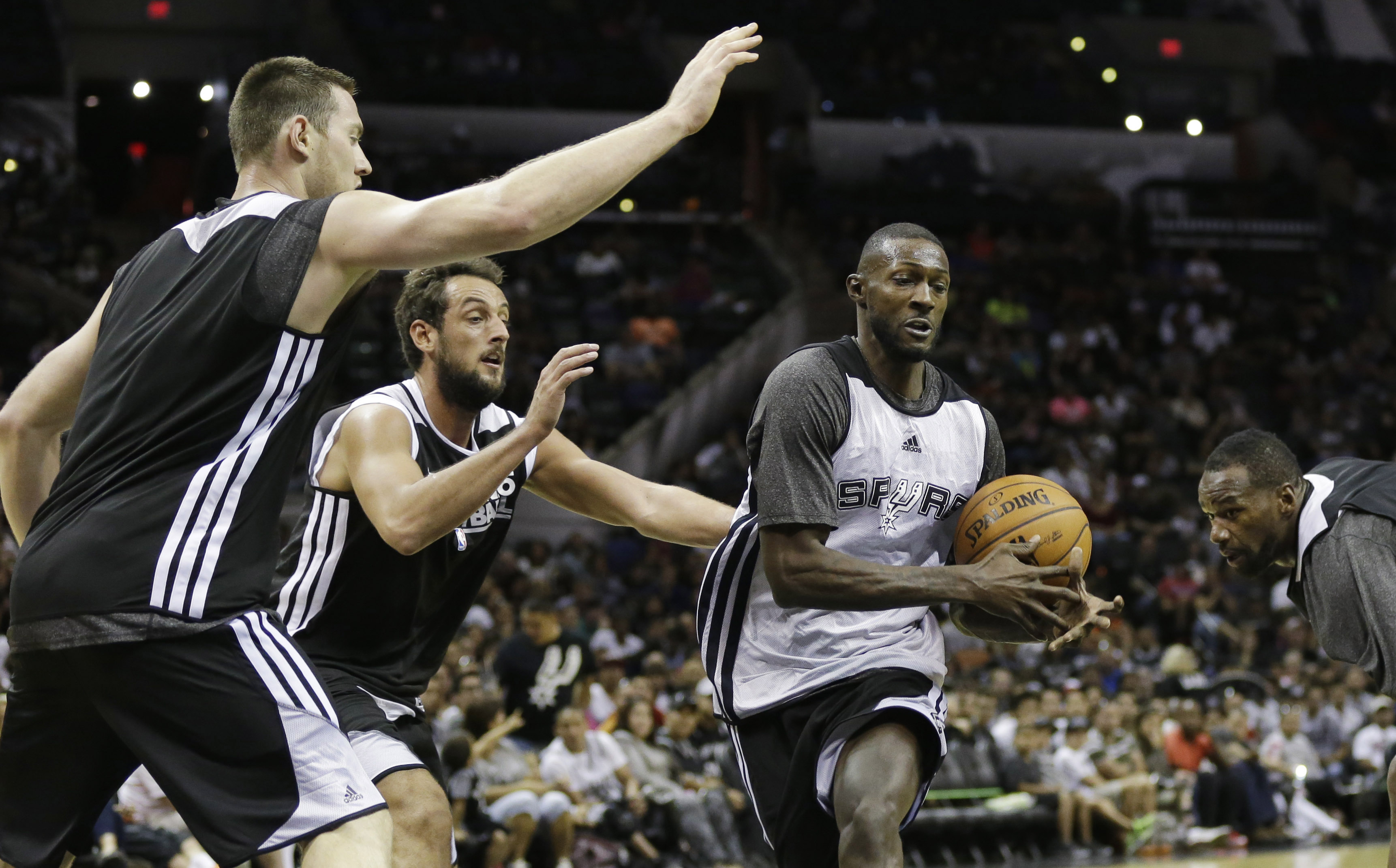 San Antonio Spurs' Courtney Fells, right, is defended by Spurs' Aron Baynes, left, of Australia, and Marco Belinelli, of Italy, during an open NBA basketball practice, Sunday, Oct. 6, 2013, in San Antonio