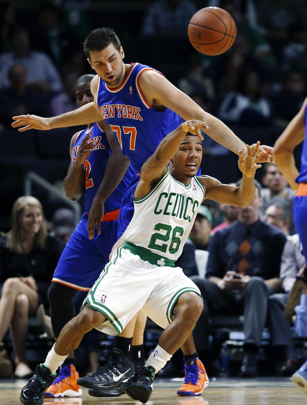 Boston Celtics guard Phil Pressey (26) passes the ball against the defense of New York Knicks forward Andrea Bargnani (77) during the first half of a preseason NBA basketball game in Providence, R.I., Wednesday, Oct. 9, 2013