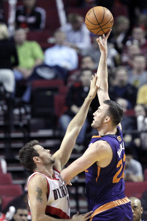 Phoenix Suns center Miles Plumlee, right, shoots over Portland Trail Blazers forward Joel Freeland during the second half of an NBA preseason basketball game in Portland, Ore., Wednesday, Oct. 9, 2013.  Plumlee came off the bench to score nine points as the Suns won 104-98