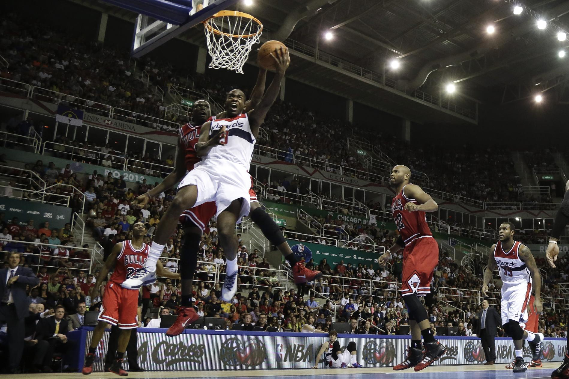 Washington Wizards' Martell Webster, top right, makes a move to the basket as he is guarded by Chicago Bulls' Luol Deng  during the second half of an NBA preseason basketball game in Rio de Janeiro, Brazil, Saturday, Oct. 12, 2013. Chicago Bulls defeated Washington Wizards 83-81