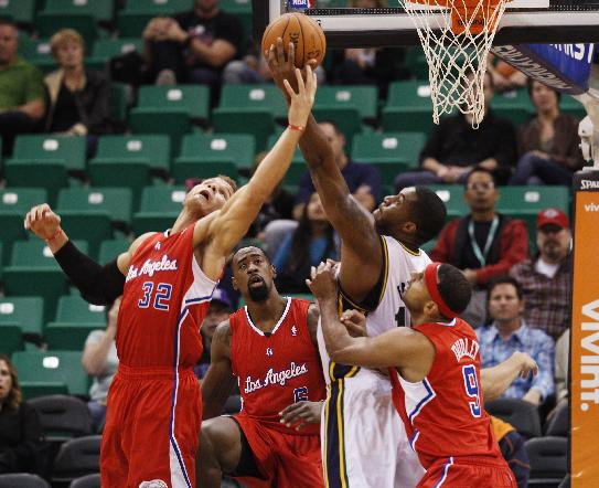 Los Angeles Clippers' Blake Griffin, left, and Utah Jazz's Derrick Favors, middle right, compete for a rebound in the first half during an NBA preseason basketball game Saturday, Oct. 12, 2013, in Salt Lake City