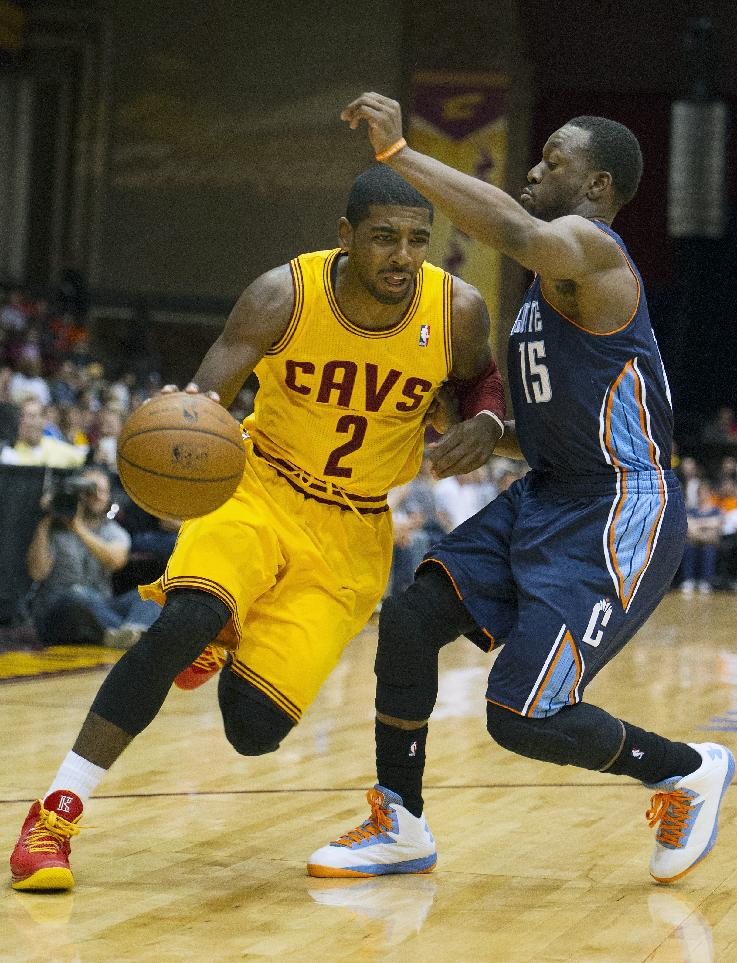 Cleveland Cavaliers guard Kyrie Irving (2) drives past Charlotte Bobcats defender Kemba Walker during the first quarter of an NBA preseason basketball game in Canton, Ohio on Tuesday, Oct. 15, 2013