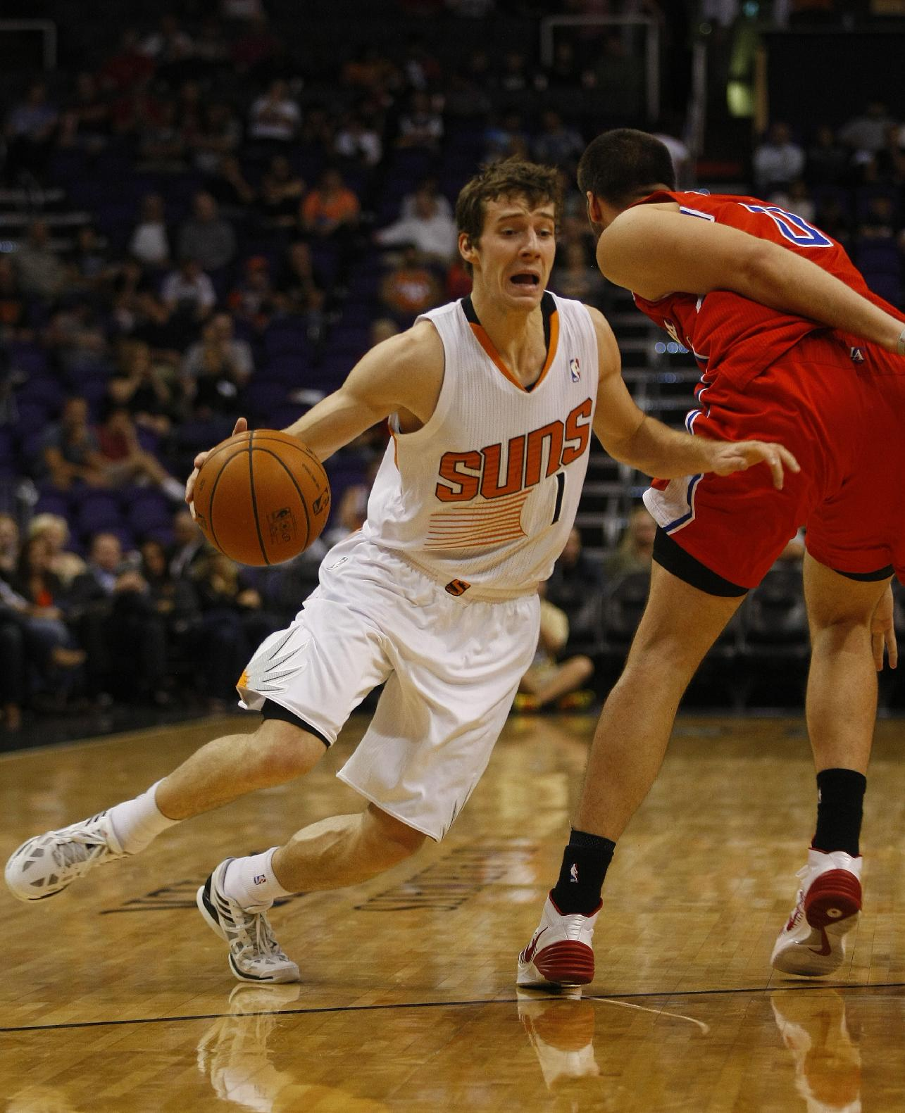 Phoenix Suns point guard Goran Dragic (1) drives past Los Angeles Clippers center Byron Mullens (0) in the third quarter during an NBA preseason basketball game on Tuesday, Oct. 15, 2013, in Phoenix