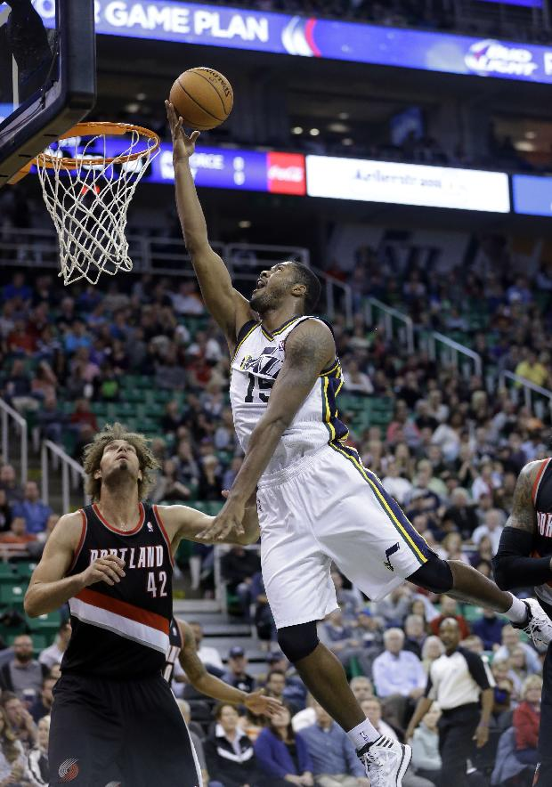Utah Jazz's Derrick Favors (15) lays the ball up as Portland Trail Blazers' Robin Lopez (42) looks on in the second half during an NBA preseason basketball game Wednesday, Oct. 16, 2013, in Salt Lake City. The Trail Blazers won 99-92