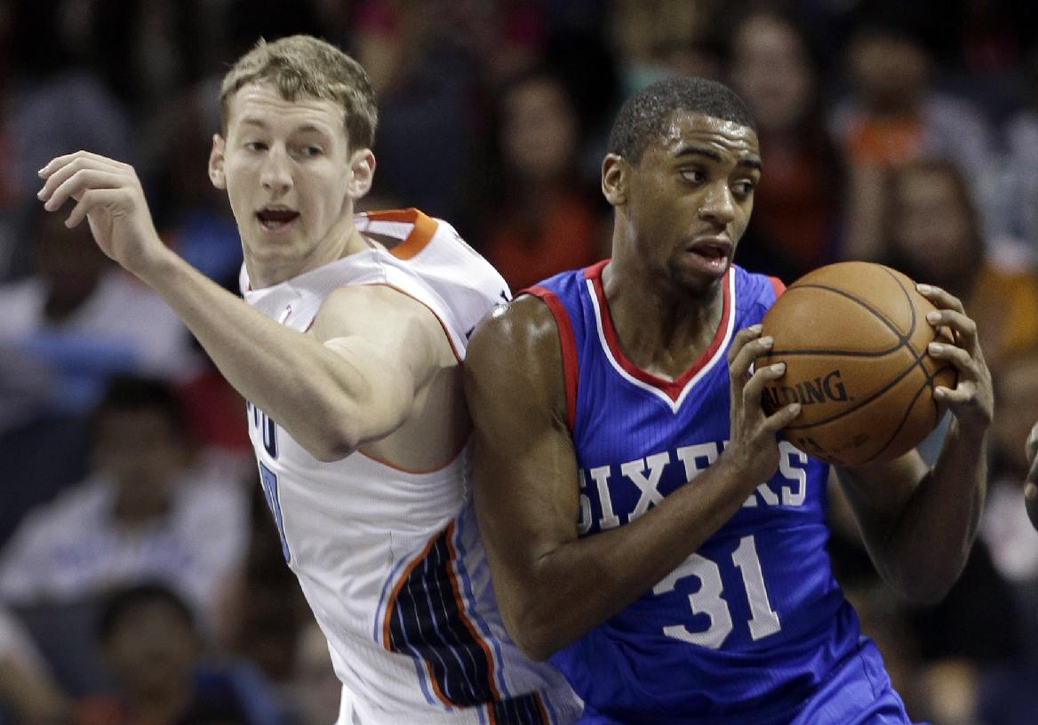 Philadelphia 76ers' Hollis Thompson, right, grabs a rebound in front of Charlotte Bobcats' Cody Zeller, left, during the second half of a preseason NBA basketball game in Charlotte, N.C., Thursday, Oct. 17, 2013. The Bobcats won 110-84