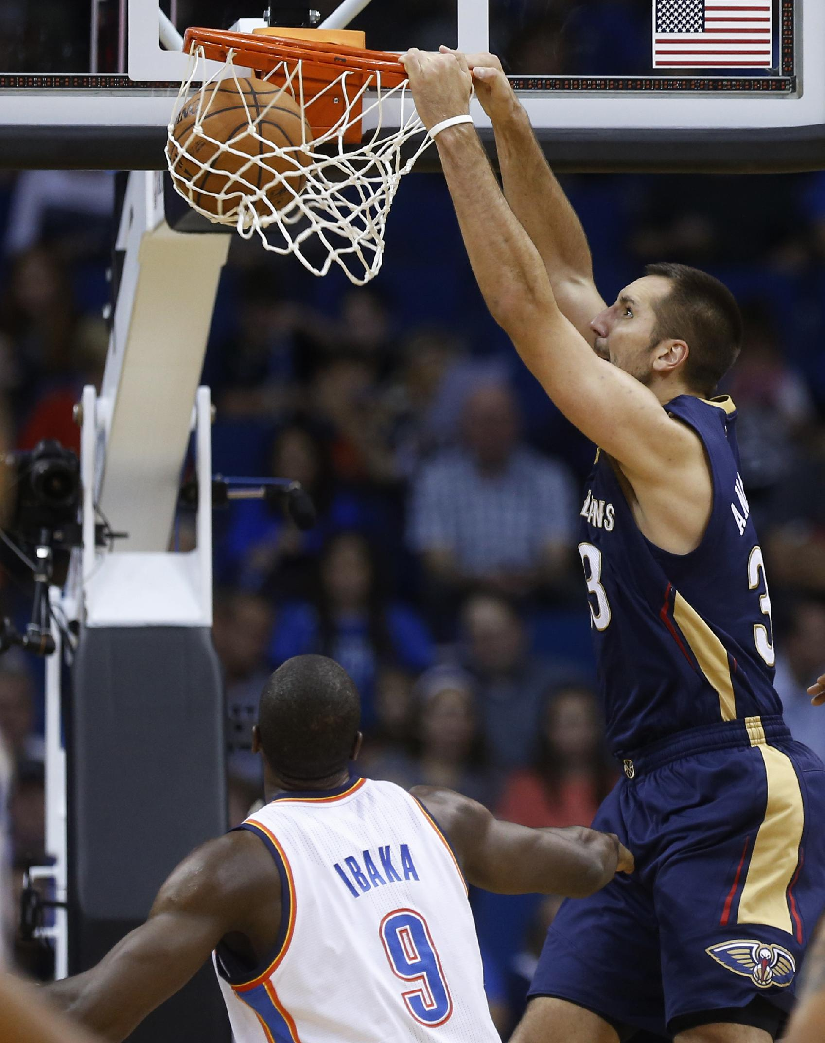 New Orleans Pelicans forward Ryan Anderson (33) dunks in front of Oklahoma City Thunder forward Serge Ibaka (9) in the third quarter of an NBA basketball preseason game in Tulsa, Okla., Thursday, Oct. 17, 2013. New Orleans won 105-102