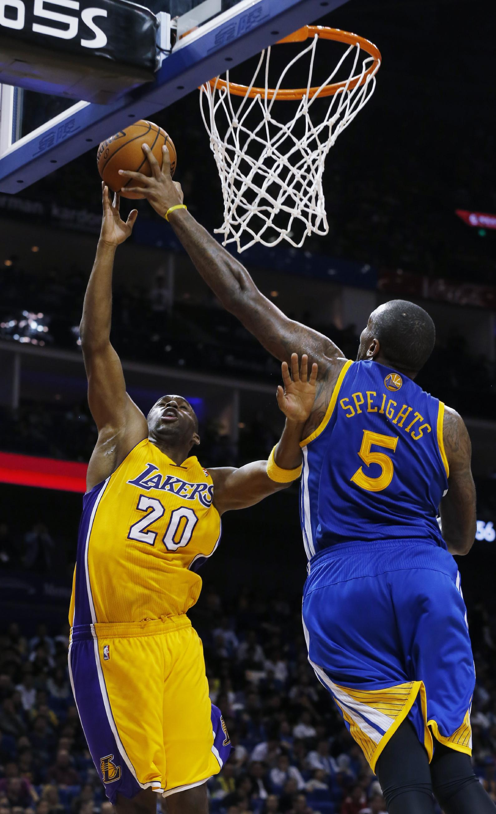 Jodie Meeks of Los Angeles Lakers, left, is blocked by Marreese Speights of Golden State Warriors during a 2013-2014 NBA preseason game between Lakers and Warriors at Mercedes-Benz Arena in Shanghai, China, Friday, Oct. 18, 2013