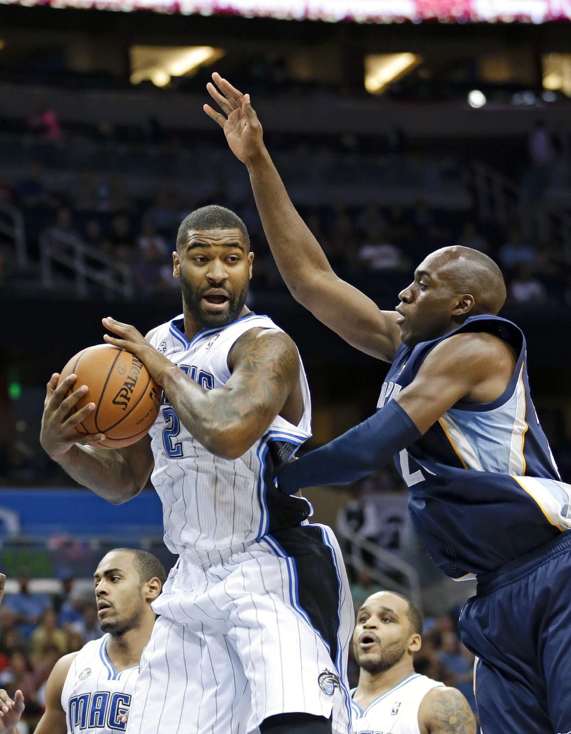 Orlando Magic's Kyle O'Quinn, left, grabs a rebound in front of Memphis Grizzlies' Quincy Pondexter, right, during the first half of an NBA preseason basketball game in Orlando, Fla., Friday, Oct. 18, 2013