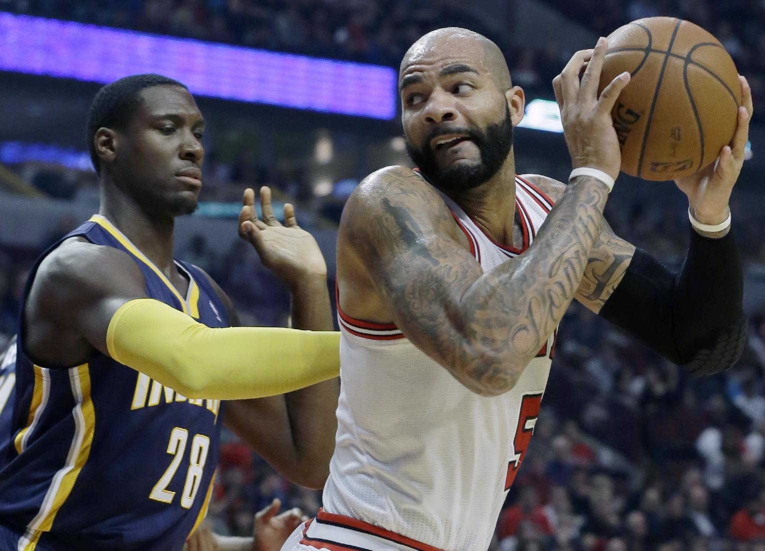 Chicago Bulls forward Carlos Boozer (5) looks to the basket as Indiana Pacers center Ian Mahinmi (28) guards during the first half of an NBA preseason basketball game in Chicago on Friday, Oct. 18, 2013