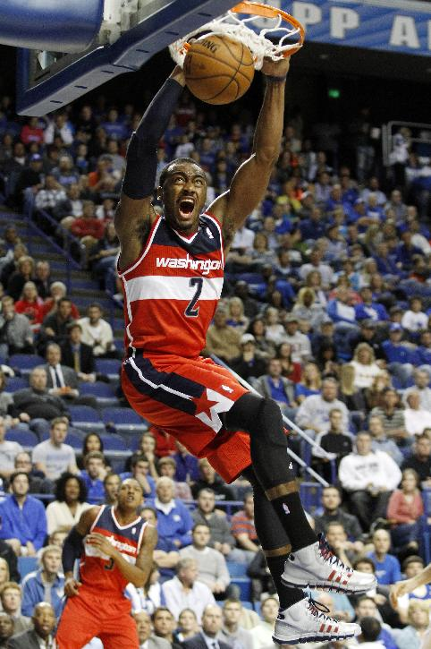 Washington's John Wall dunks during an NBA basketball exhibition game against New Orleans, Saturday, Oct. 19, 2013, in Lexington, Ky