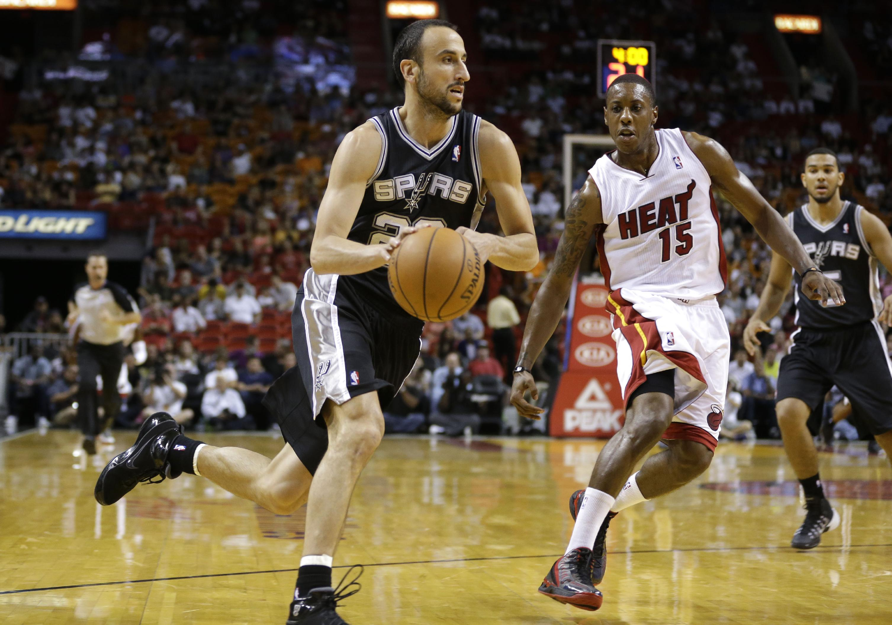 San Antonio Spurs' Manu Ginobili, left, drives to the basket past Miami Heat's Mario Chalmers (15) during the first half of an NBA preseason basketball game, Saturday, Oct. 19, 2013, in Miami