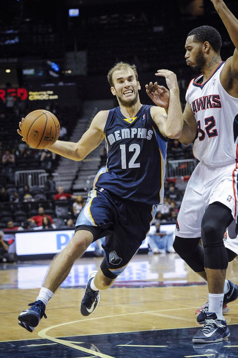 Memphis Grizzlies' Nick Calathes (12) drives against the defense of Atlanta Hawks forward Mike Scott (32) during the second half of an NBA preseason basketball game, Sunday, Oct. 20, 2013, in Atlanta