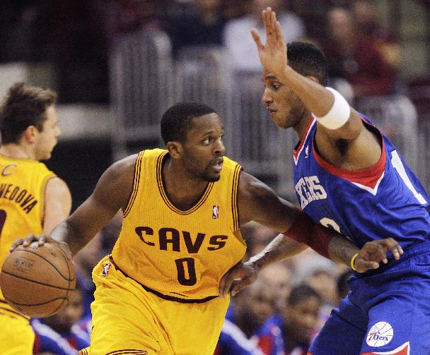 Cleveland Cavaliers' C.J. Miles, left, looks for an open pass as Philadelphia 76ers' Evan Turner defends during the second quarter of an NBA preseason basketball game Monday, Oct. 21, 2013, in Columbus, Ohio
