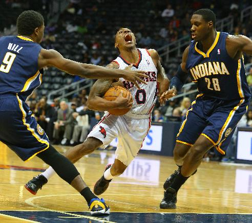 Indiana Pacers small forward Solomon Hill (9) and center Ian Mahinmi (28) double team Atlanta Hawks point guard Jeff Teague as he attempts to drive the lane during the second half of a preseason NBA basketball game on Tuesday, Oct. 22, 2013, in Atlanta