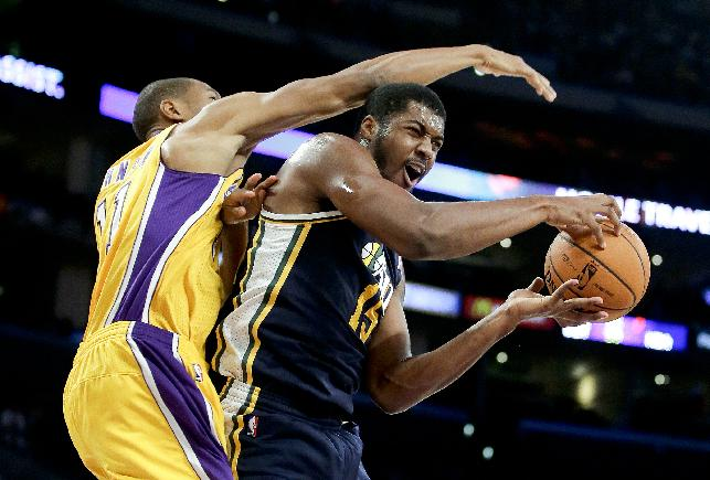 Utah Jazz forward Derrick Favors, right, pulls a rebound away from Los Angeles Lakers guard Wesley Johnson during the first half of a preseason NBA basketball game in Los Angeles, Tuesday, Oct. 22, 2013