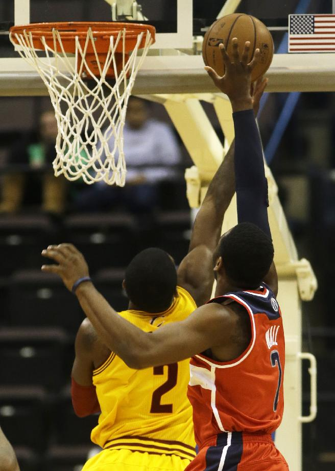 Washington Wizards point guard John Wall, right, blocks a shot by Cleveland Cavaliers point guard Kyrie Irving, left, in the first half of an NBA preseason basketball game on Wednesday, Oct. 23, 2013, in Cincinnati