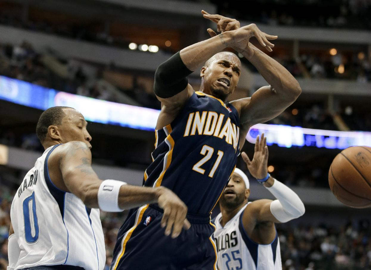 Indiana Pacers' David West (21) loses the ball against Dallas Mavericks' Shawn Marion (0) and Vince Carter (25) on a drive to the basket in the second half of a preseason NBA basketball game, Friday, Oct. 25, 2013, in Dallas. The Pacers won 98-77