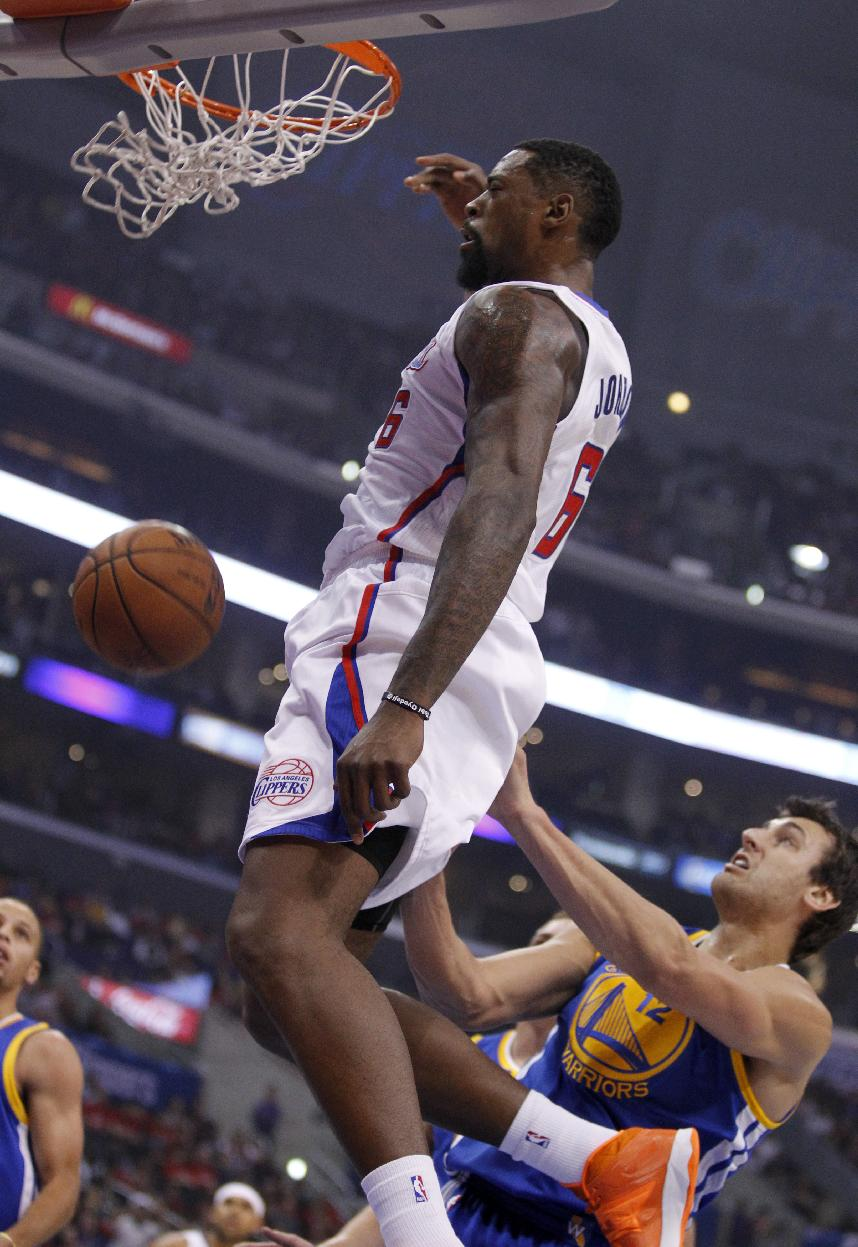 Los Angeles Clippers center DeAndre Jordan, left, dunks over Golden State Warriors center Andrew Bogut, right, of Australia, defending during an NBA basketball game on Thursday, Oct. 31, 2013, in Los Angeles