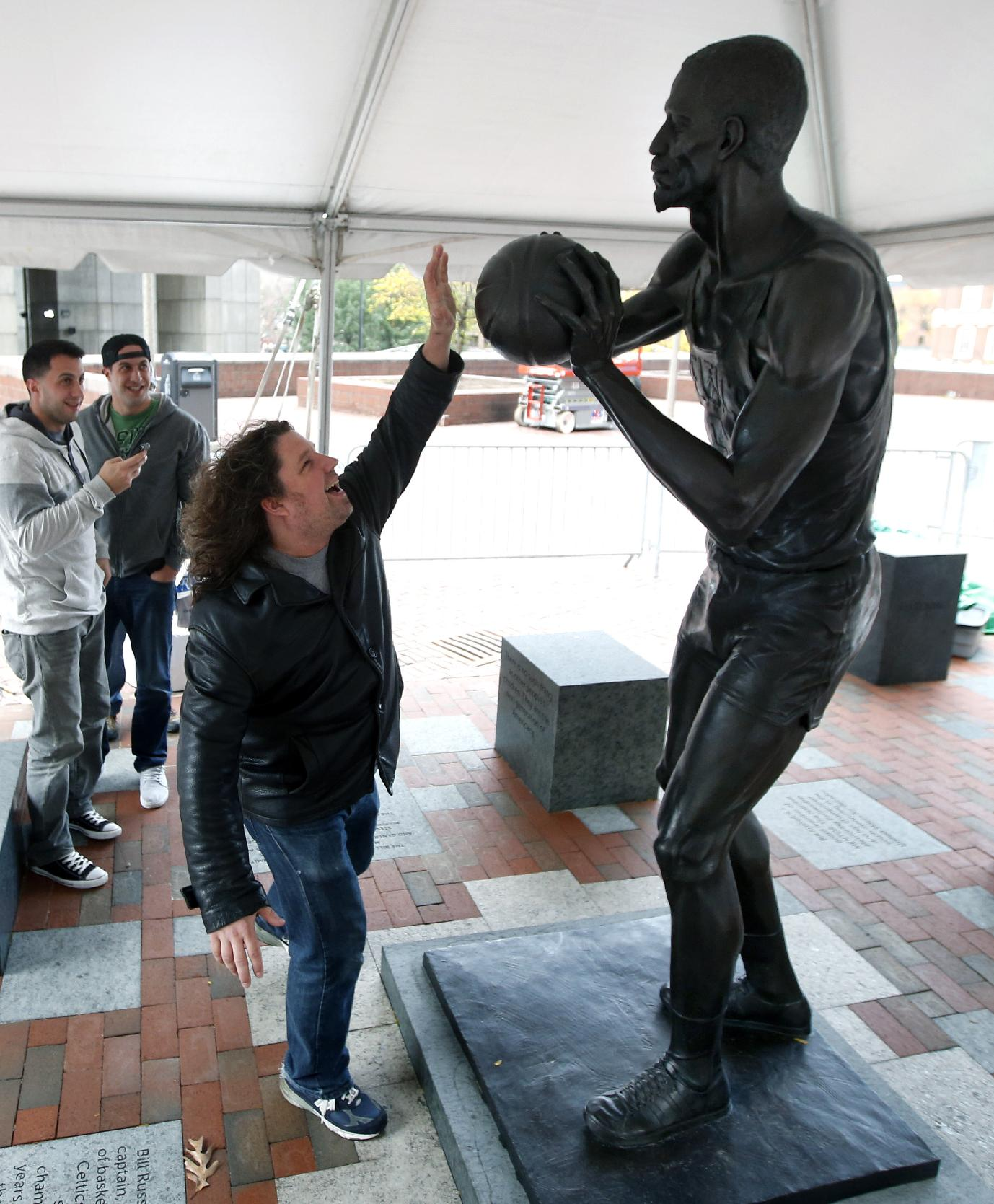 Scott Damgaard, of Boston, reaches up to a statue of former Boston Celtics basketball star Bill Russell after it was unveiled at City Hall Plaza in Boston, Friday, Nov. 1, 2013
