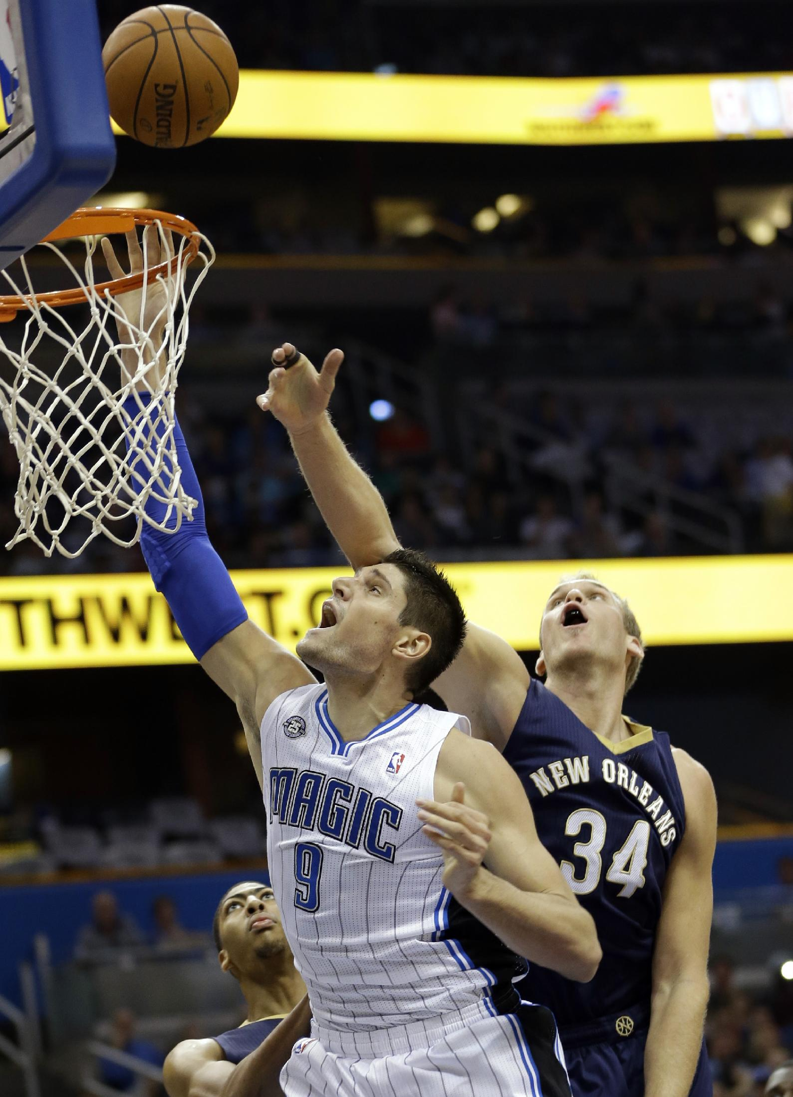 Orlando Magic's Nikola Vucevic (9), of Montenegro, makes a shot in front of New Orleans Pelicans' Greg Stiemsma (34) during the first half of an NBA basketball game in Orlando, Fla., Friday, Nov. 1, 2013