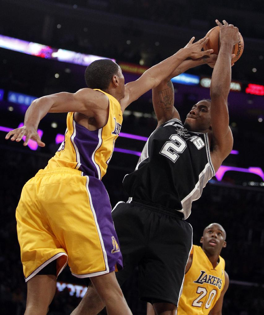 Los Angeles Lakers guard Wesley Johnson, left, gets his hand on a shot by San Antonio Spurs forward Kawhi Leonard (2) with Lakers guard Jodie Meeks (20) looking on in the fourth quarter during an NBA basketball game on Friday, Nov. 1, 2013, in Los Angeles. The Spurs won 91-85