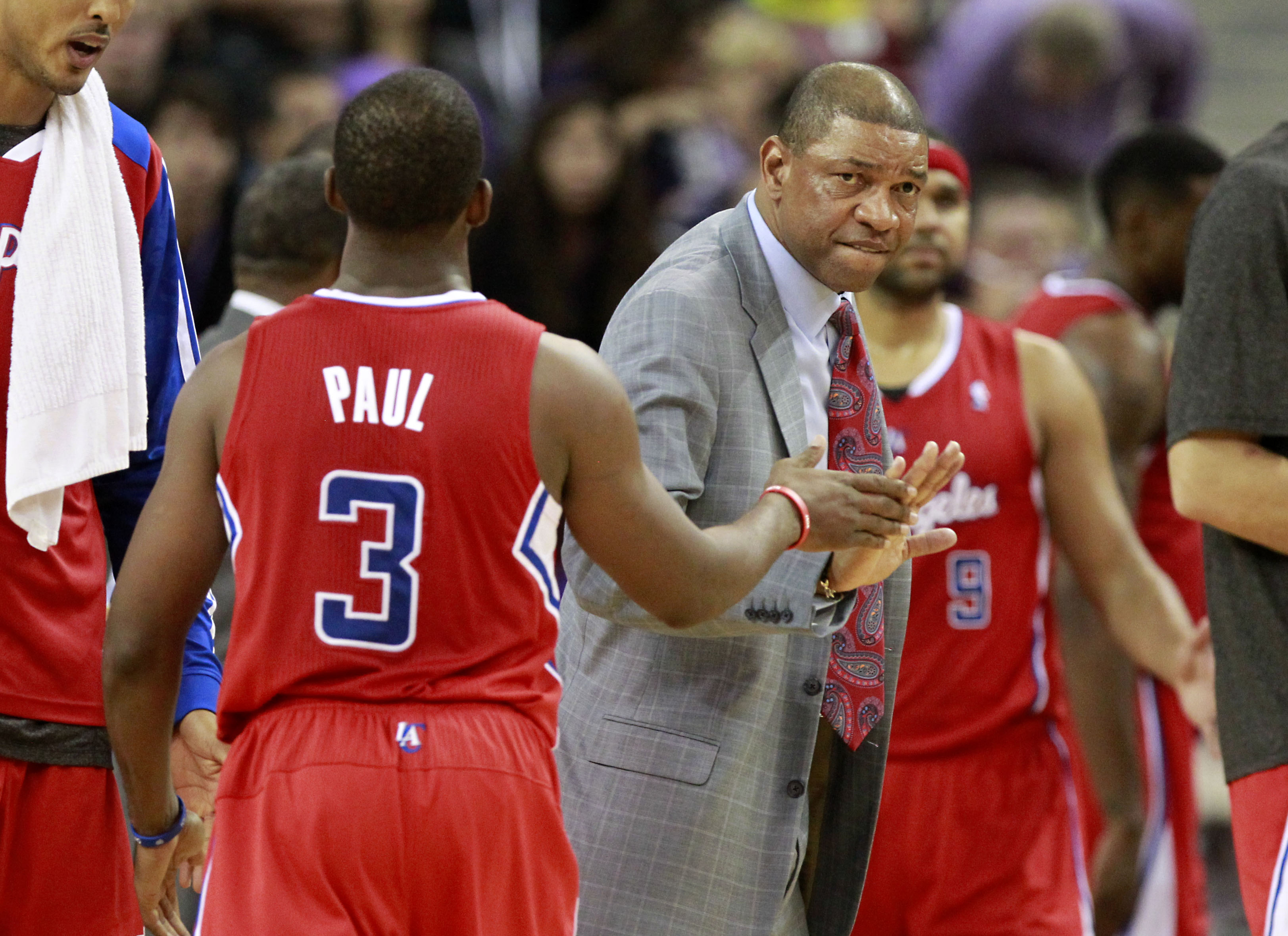 Los Angeles Clippers guard Chris Paul, left, slaps hands with head coach Doc Rivers as he walks off the court during a timeout in the closing moments of a 110-101 win over the Sacramento Kings in an NBA basketball game in Sacramento, Calif., Friday, Nov. 1, 2013