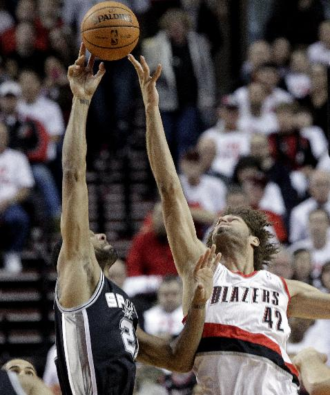 San Antonio Spurs forward Tim Duncan, left, shoots over Portland Trail Blazers center Robin Lopez during the first half of an NBA basketball game in Portland, Ore., Saturday, Nov. 2, 2013