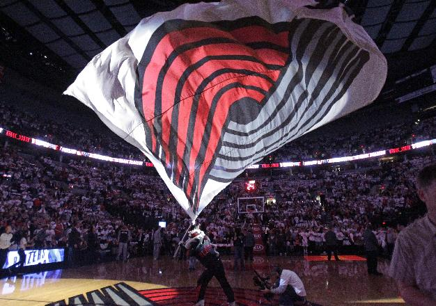 Portland Trail Blazers mascot Blaze waves the team flag for the NBA basketball team's home-opener against the San Antonio Spurs in Portland, Ore., Saturday, Nov. 2, 2013