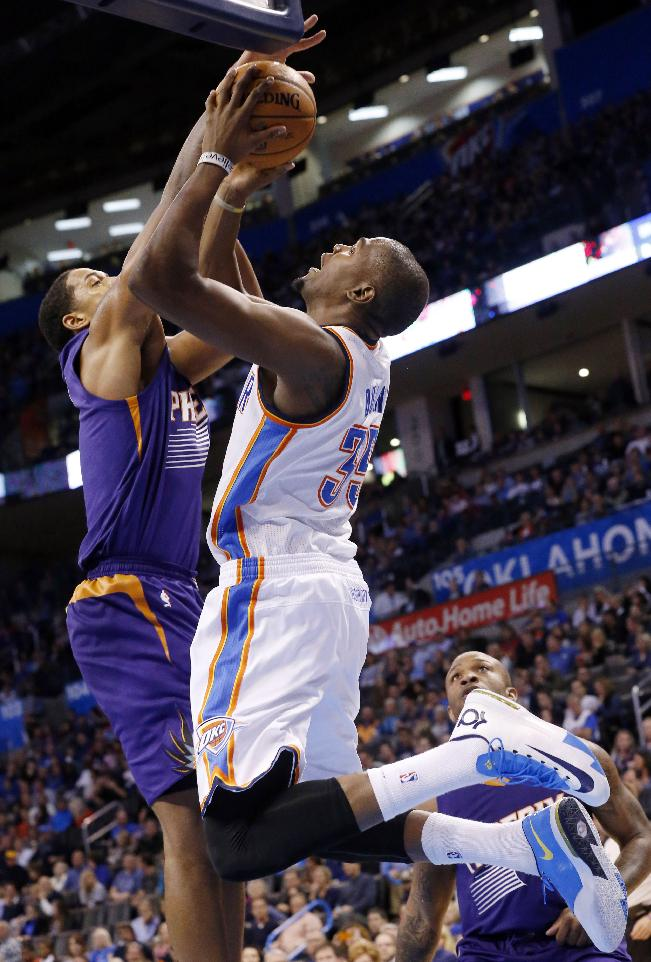 Oklahoma City Thunder forward Kevin Durant, right, is fouled by Phoenix Suns forward Channing Frye, left, as he shoots in the third quarter of an NBA basketball game in Oklahoma City, Sunday, Nov. 3, 2013. Oklahoma City won 103-96