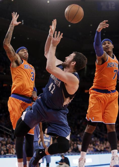 Minnesota Timberwolves' Kevin Love (42) shoots over New York Knicks' Kenyon Martin (3) and Carmelo Anthony (7) during the second half of an NBA basketball game Sunday, Nov. 3, 2013, in New York. The Timberwolves won 109-100