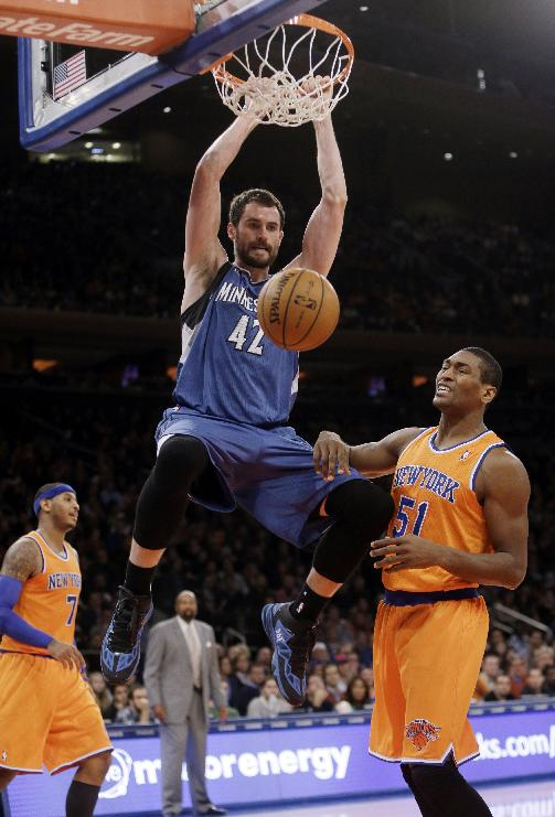 Minnesota Timberwolves' Kevin Love (42) dunks the ball as New York Knicks' Metta World Peace (51) reacts during the second half of an NBA basketball game Sunday, Nov. 3, 2013, in New York. The Timberwolves won 109-100