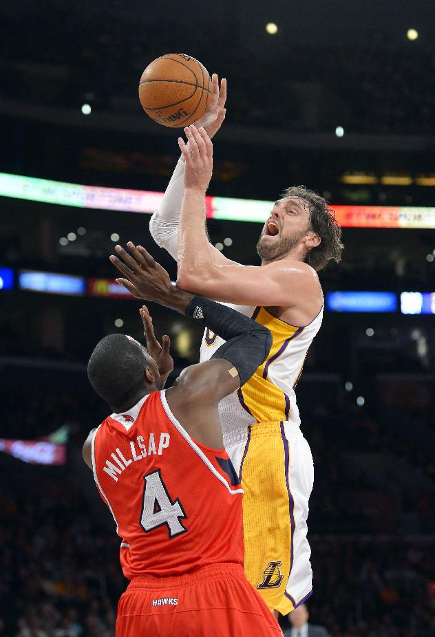Los Angeles Lakers forward Pau Gasol, top, of Spain, puts up a shot as Atlanta Hawks forward Paul Millsap defends during the first half of their NBA basketball game, Sunday, Nov. 3, 2013, in Los Angeles