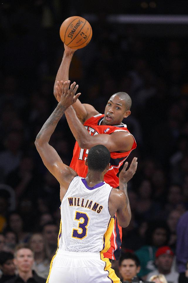 Atlanta Hawks center Al Horford, top, of the Dominican Republic, passes the ball over Los Angeles Lakers forward Shawne Williams during the first half of an NBA basketball game Sunday, Nov. 3, 2013, in Los Angeles