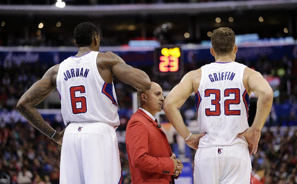 A security guard stands between Los Angeles Clippers' Blake Griffin, right, and DeAndre Jordan during the second half of an NBA basketball game against the Houston Rockets on Monday, Nov. 4, 2013, in Los Angeles. The Clippers won 137-118