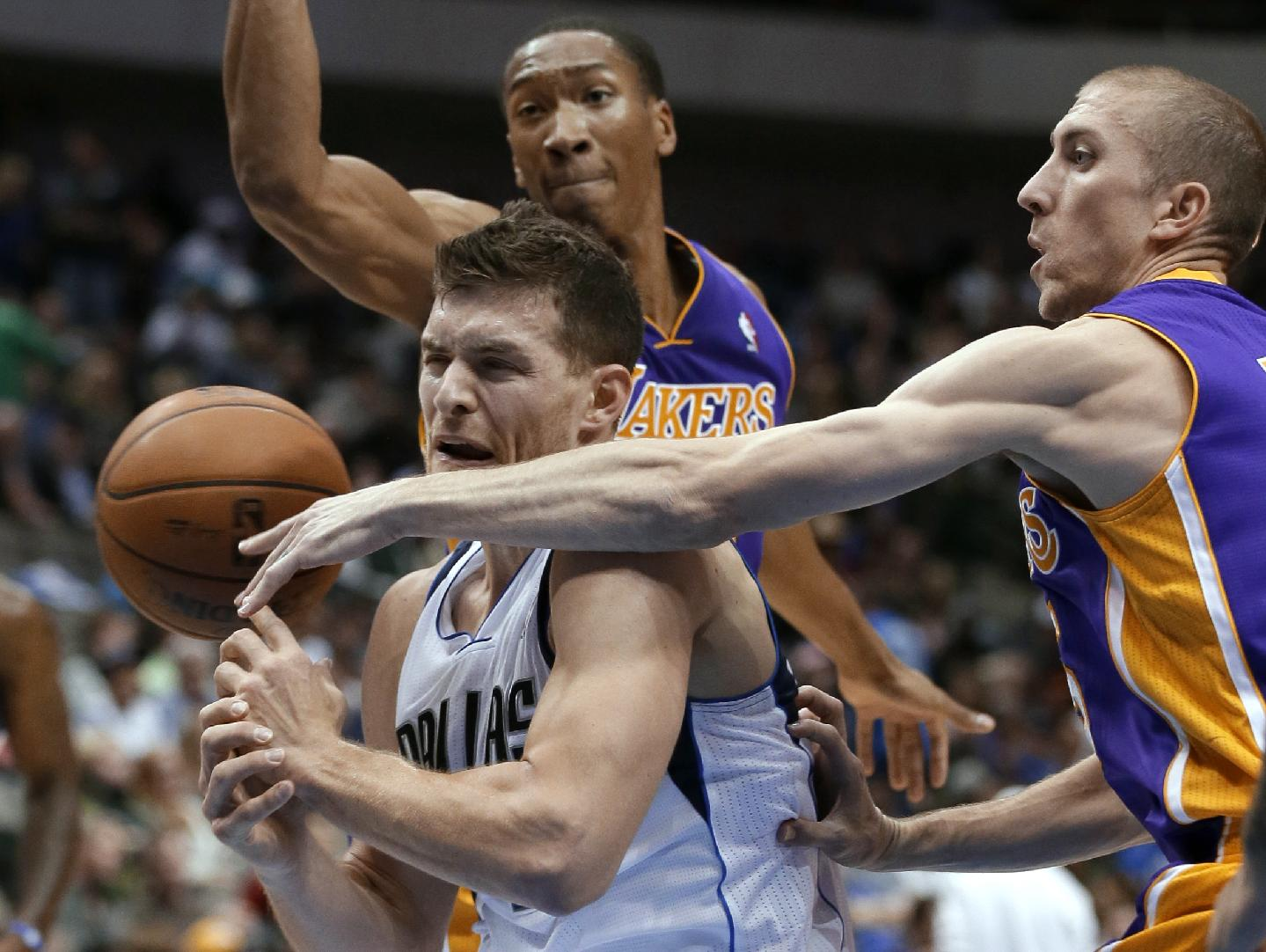 Dallas Mavericks' Gal Mekel, left, of Israel, has the ball knocked away on a drive to the basket by Los Angeles Lakers' Steve Blake, right, as Wesley Johnson, rear, helps defend during the second half of an NBA basketball game, Tuesday, Nov. 5, 2013, in Dallas. The Mavericks won 123-104