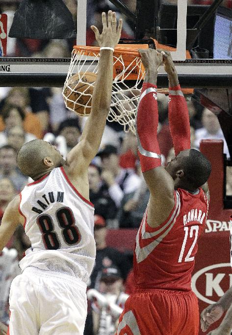 Houston Rockets forward Dwight Howard, right, scores against Portland Trail Blazers forward Nicolas Batum, from France, during the second half of an NBA basketball game in Portland, Ore., Tuesday, Nov. 5, 2013.  Howard scored 29 points and pulled in 13 rebounds as they beat the Trail Blazers 116-101