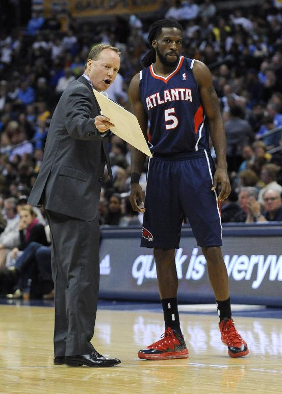 Atlanta Hawks forward DeMarre Carroll (5) listens to coach Mike Budenholzer during the second quarter of an NBA basketball game against the Denver Nuggets on Thursday, Nov. 7, 2013, in Denver