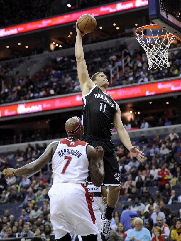 Brooklyn Nets center Brook Lopez (11) goes to the basket against Washington Wizards forward Al Harrington (7) during the first half of an NBA basketball game Friday, Nov. 8, 2013, in Washington