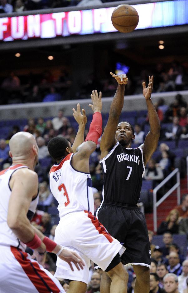 Brooklyn Nets guard Joe Johnson (7) puts up a shot against Washington Wizards guard Bradley Beal (3) and Marcin Gortat, of Poland, during the first half of an NBA basketball game Friday, Nov. 8, 2013, in Washington